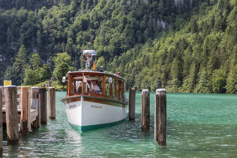 Launch with tourists mooring to wooden pier in lake Konigssee stock image