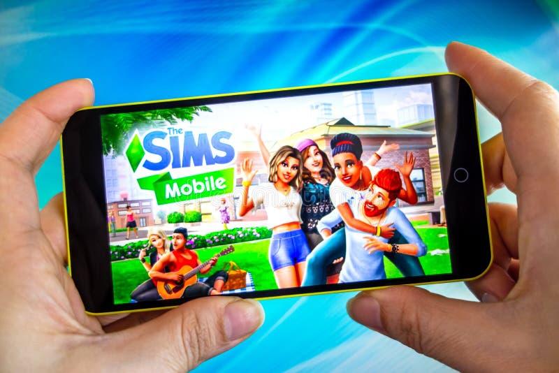 Berdyansk Ukraina - mars 4, 2019 - slut upp av handen av personen som spelar The Sims den mobila modiga apllicationen arkivbild