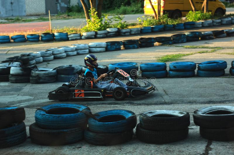 Berdyansk, Ukraine - JULY 13, 2019: Karting for children to rest and learn proper and careful driving on the road. Young driver in helmet at the wheel of the royalty free stock photos