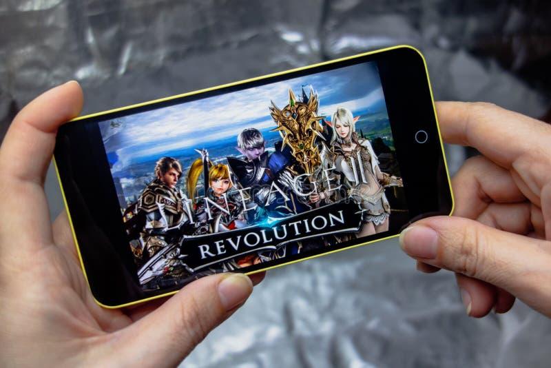 Berdyansk, Ukraine - 16 mars 2019 : Mains tenant un smartphone avec la lignée jeu de 2 révolutions sur l'écran de visualisation photographie stock