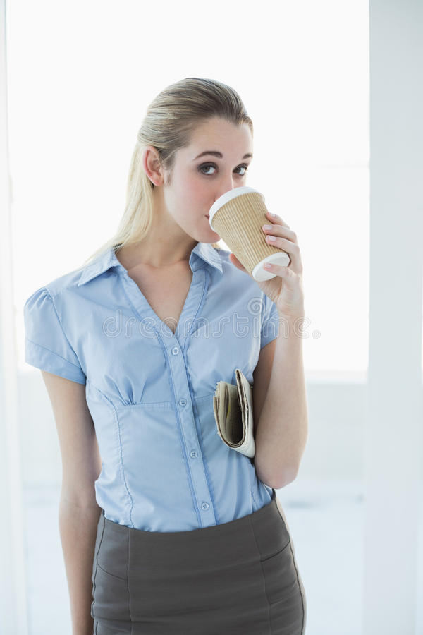 Bere elegante contento della donna di affari della tazza eliminabile che tiene un giornale immagini stock libere da diritti
