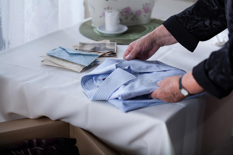 Bereaved female tidying things stock photos