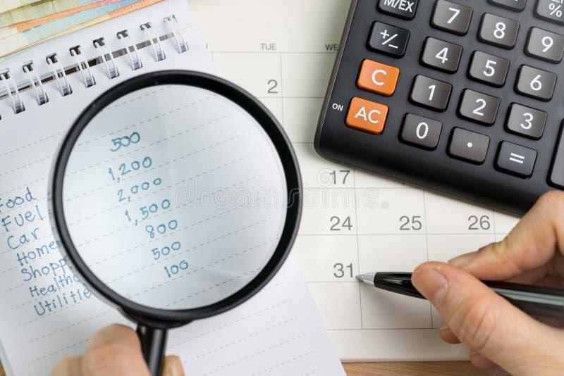 Berechnung der persönlichen Ausgabe oder Abrechnungstagkonzept, Vergrößerungs-glas lizenzfreie stockfotografie