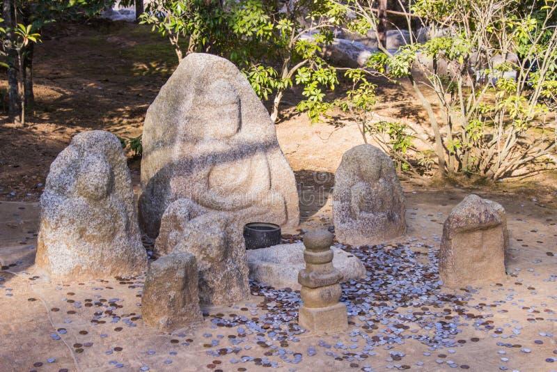 Bereich an den Touristenwurfsmünzen für beten Segen von Stein-Buddha an den Carvings innerhalb des Gartens von Kinkakuji-Tempel K stockbilder