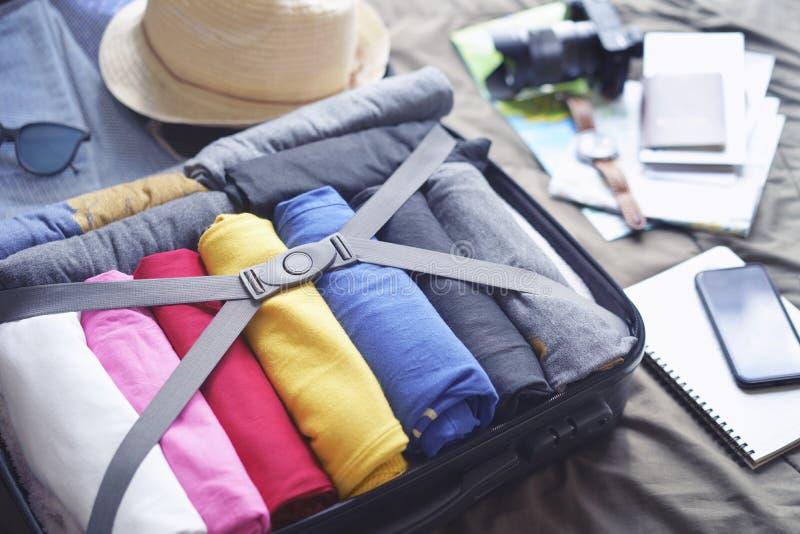 Bereid toebehoren voor nieuwe reis voor en reis naar lange weekendreis, inpakkend kleren in kofferzak op bed stock foto