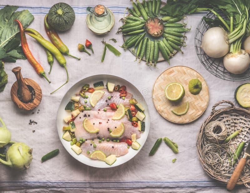 Bereiding van de vis voor het koken met rauwe goede visfilet in witte bakpan op bijtende tafel met verschillende groenten, bovena royalty-vrije stock afbeeldingen