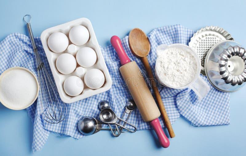 Bereiding voor het bakken Ingrediënten en keukenartikelen voor het bakken Keukengerei, meel, eieren, suiker stock afbeelding