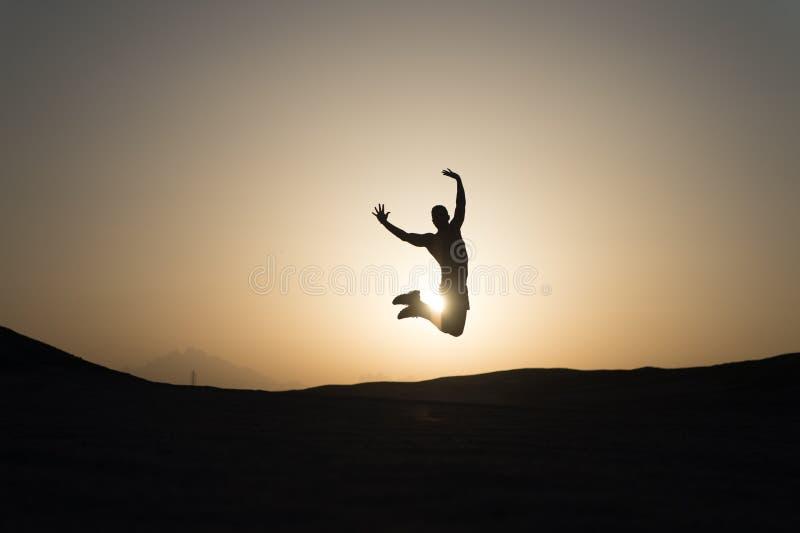 Bereik hoofddoel De motiesprong van de silhouetmens voor de achtergrond van de zonsonderganghemel Het toekomstige succes hangt va stock afbeelding