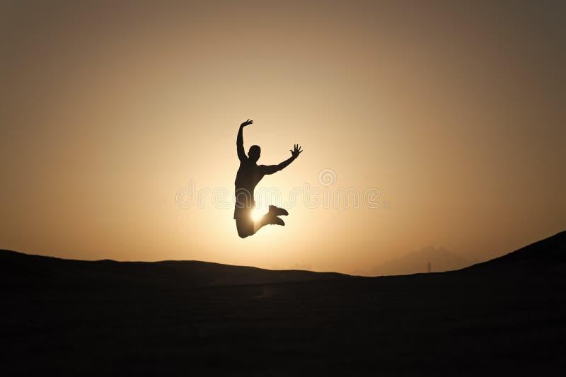 Bereik hoofddoel De motiesprong van de silhouetmens voor de achtergrond van de zonsonderganghemel Het toekomstige succes hangt va royalty-vrije stock fotografie