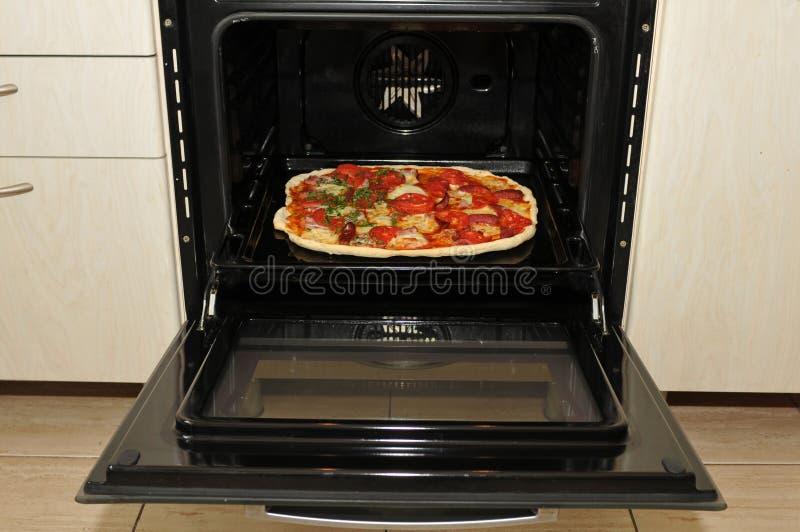 Bereite Pizza im Ofen stockbild