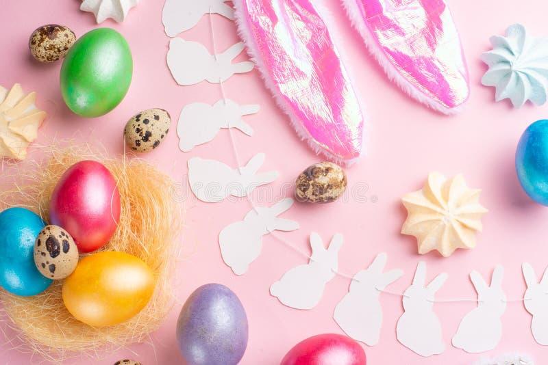 Bereiten Sie für Produktmontageanzeige vor Ostereier gefärbt mit den Hasenohren auf einem rosa Hintergrund mit Bonbons Flache Lag stockbild