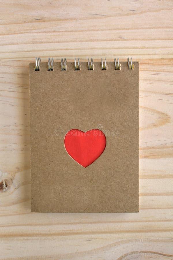 Bereiten Sie Notizbuch mit roter Herzform auf hölzernem Schreibtisch auf stockfoto