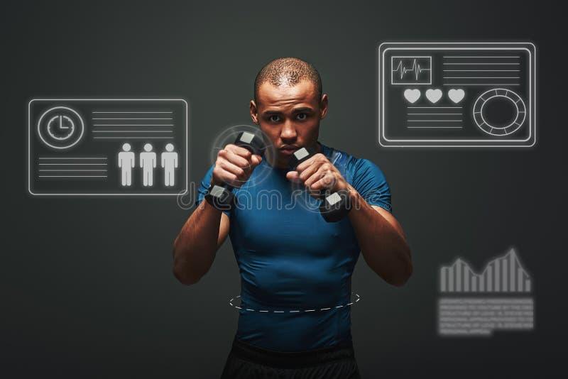 Bereiten Sie vor, um den hübschen jungen Sportler zu kämpfen, der mit Dummköpfen über dunklem Hintergrund ausarbeitet Spielkonzep lizenzfreie stockbilder