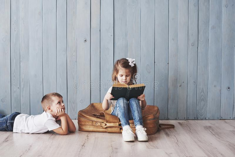 Bereiten Sie zur großen Reise vor Glückliches kleines Mädchen- und Jungenleseinteressantes Buch, das einen großen Aktenkoffer und lizenzfreies stockbild