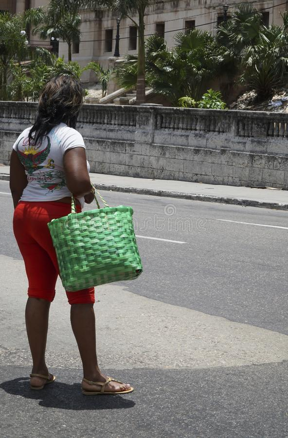 Bereitstehende Straße der kubanischen Frau, tragende grüne Tasche in Havana stockbild