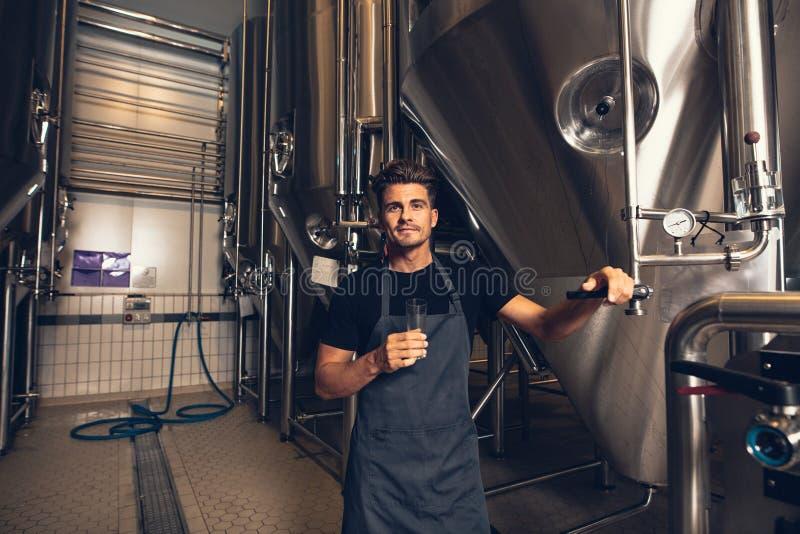Bereitstehender Behälter des männlichen Brauers in der Brauerei stockfotografie