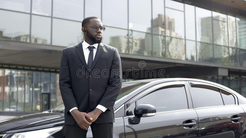 Bereitstehendes Auto des überzeugten afroen-amerikanisch Fahrers, Sicherheitsbeamteservice, Geschäft lizenzfreie stockfotos