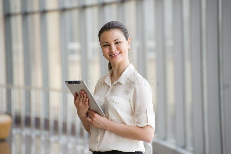 Bereitstehendes Fenster der jungen Geschäftsfrau im Büro Schönes junges weibliches Modell im hellen Büro stockfotografie