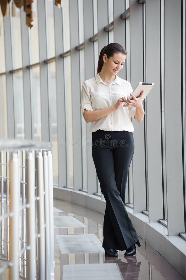 Bereitstehendes Fenster der jungen Geschäftsfrau im Büro Schönes junges weibliches Modell im hellen Büro lizenzfreies stockfoto