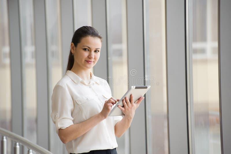 Bereitstehendes Fenster der jungen Geschäftsfrau im Büro Schönes junges weibliches Modell im hellen Büro lizenzfreie stockfotografie