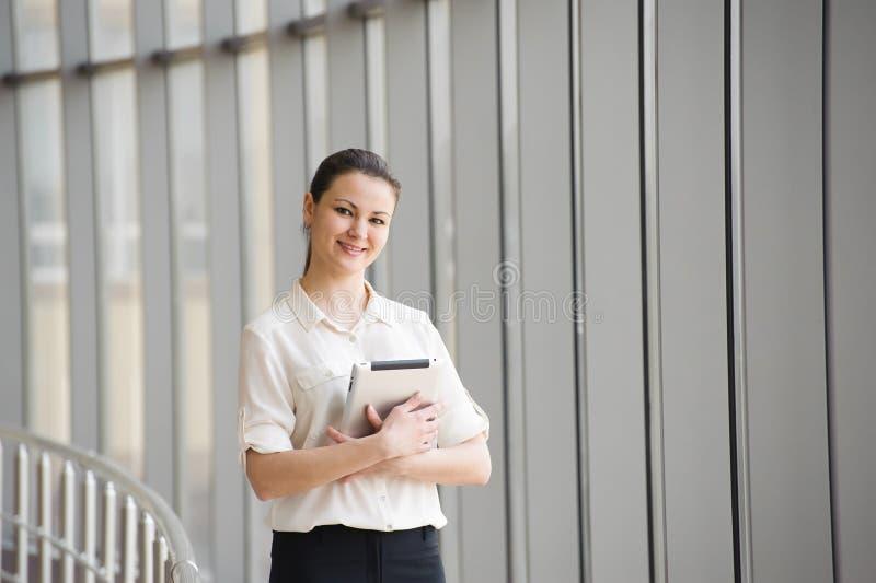 Bereitstehendes Fenster der jungen Geschäftsfrau im Büro Schönes junges weibliches Modell im hellen Büro lizenzfreie stockbilder