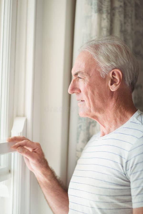 Bereitstehendes Fenster des älteren Mannes stockfotos