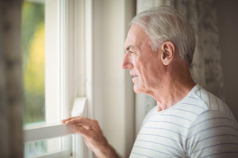 Bereitstehendes Fenster des älteren Mannes lizenzfreies stockbild