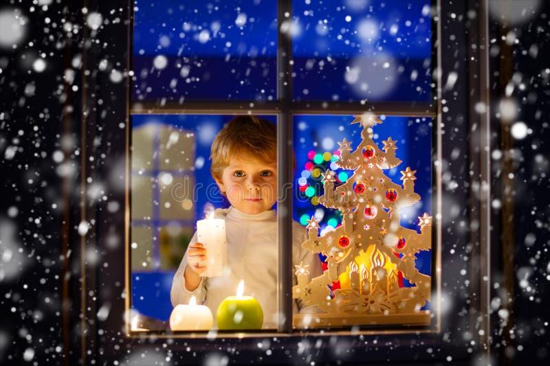 Bereitstehendes Fenster des Kleinkindjungen zur Weihnachtszeit und -c$halten stockbilder