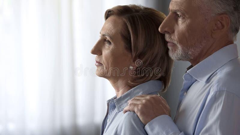 Bereitstehendes Fenster durchdachter Dame, Mann, der sie durch Schultern, die schweren Zeiten nimmt stockbilder