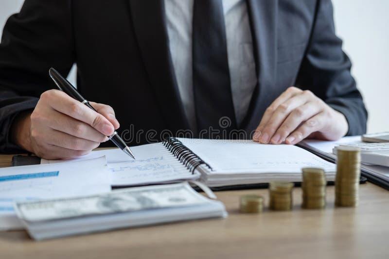 Berekenen het tellende geld van de zakenmanaccountant en het maken van nota's bij rapport die financiën doen en over investerings stock fotografie