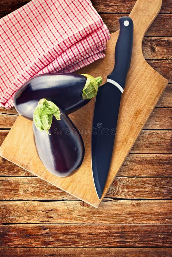 Berenjena o berenjena con el cuchillo en tablero de madera de la tajada foto de archivo libre de regalías