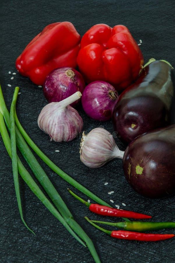 Berenjenas frescas, pimienta, ajo, cebolla en fondo negro foto de archivo