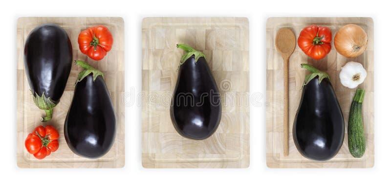 Berenjenas, tomates, calabacín, ajo y cebolla en cuttin de madera imagen de archivo libre de regalías