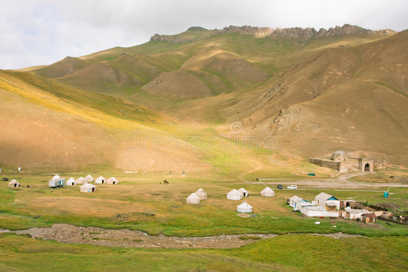 Bergäng med de asiatiska yurtsna och forntida fort Tash Rabat i Kirgizistan arkivfoto
