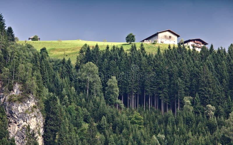 Berg in de Oostenrijkse Alpen met groen weiland en traditionele boerderij bij de hoogste en steile rotsachtige helling met donker royalty-vrije stock afbeeldingen