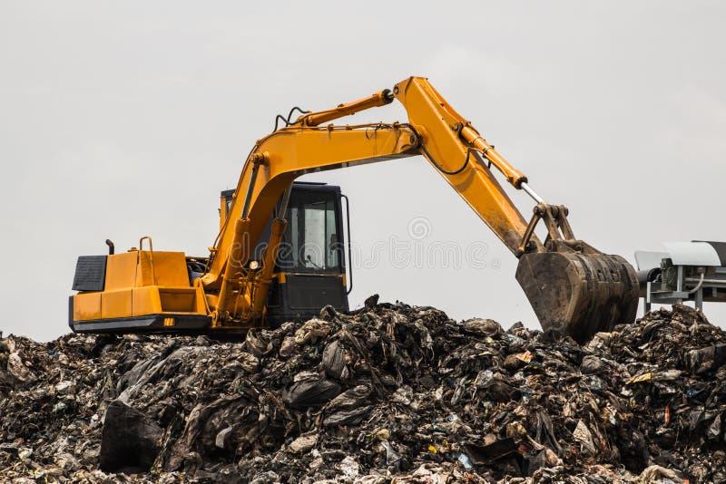 Berg des Abfalls mit dem Arbeiten lizenzfreies stockbild