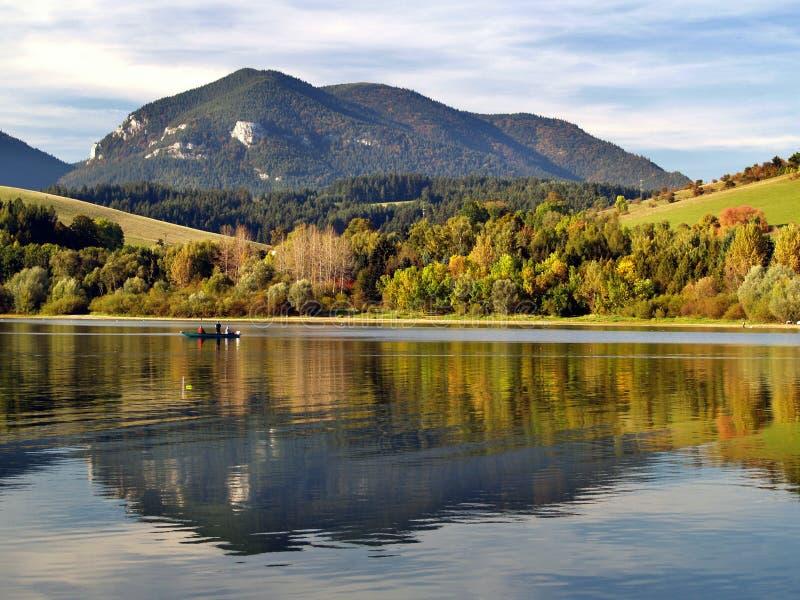 Berg die in meer wordt weerspiegeld stock afbeeldingen