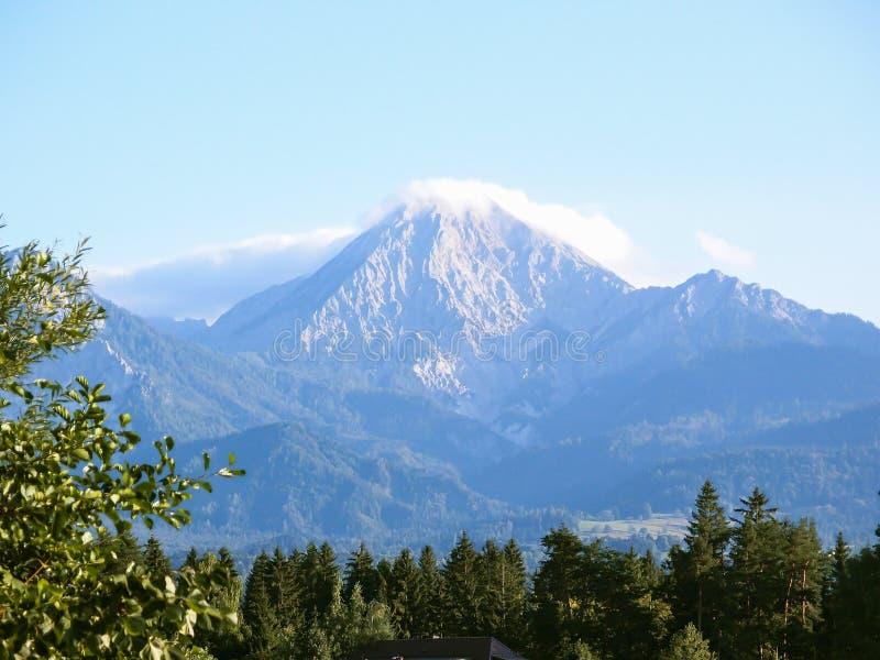 Berg eingehüllt in Nebel und in Wolken stockfotos