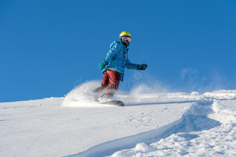 BERG ELBRUS, RUSSLAND - 30. NOVEMBER 2017: Ein Snowboardmädchen, das eine Sonnenmaske und einen Schal trägt, reitet hinunter das  stockbilder