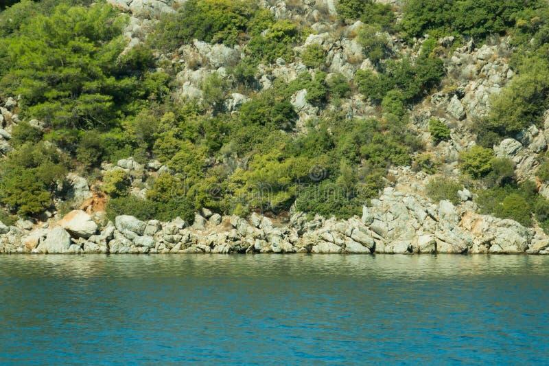Berg en Overzees kustlijn met de bos en rotsachtergrond stock afbeelding