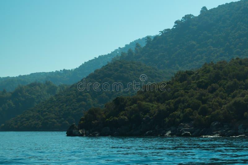 Berg en Overzees kustlijn met de bos en rotsachtergrond royalty-vrije stock afbeelding