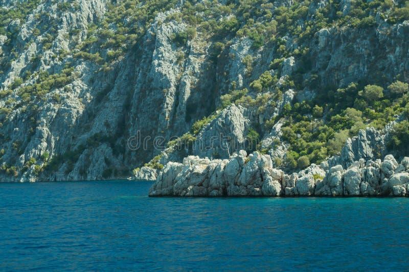 Berg en Overzees kustlijn met de bos en rotsachtergrond royalty-vrije stock fotografie
