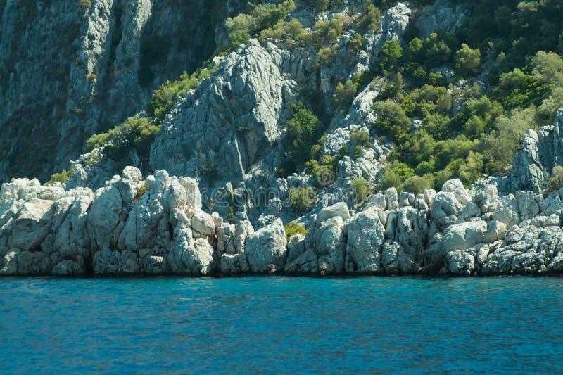 Berg en Overzees kustlijn met de bos en rotsachtergrond stock foto