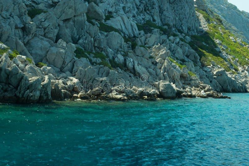 Berg en Overzees kustlijn met de overwoekerde rots stock foto's