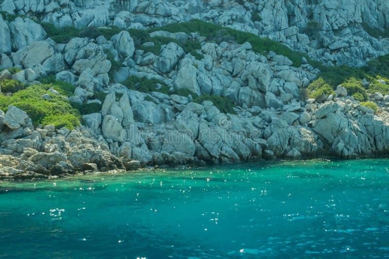 Berg en Overzees kustlijn met de overwoekerde rots royalty-vrije stock fotografie