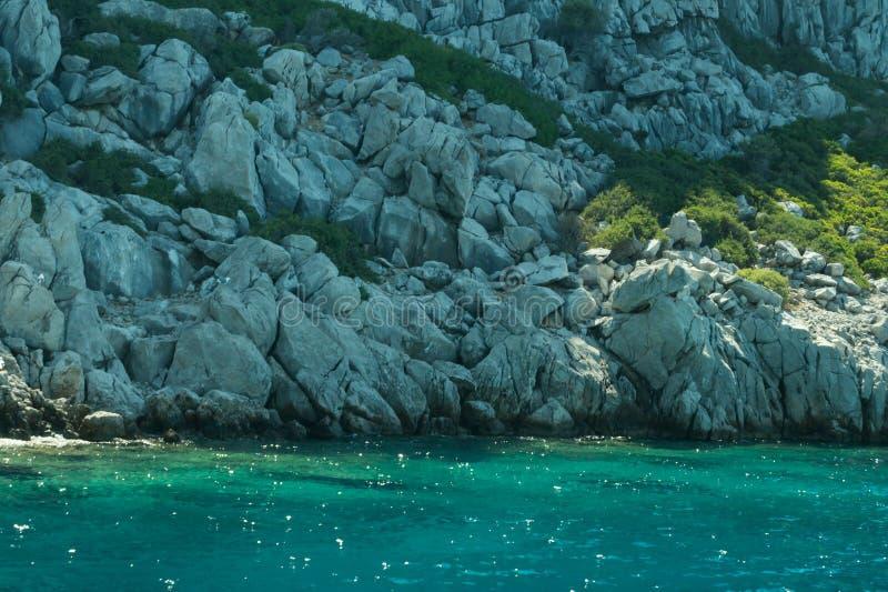 Berg en Overzees kustlijn met de overwoekerde rots royalty-vrije stock afbeelding