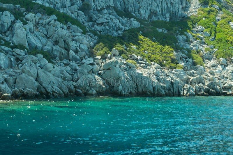 Berg en Overzees kustlijn met de overwoekerde rots royalty-vrije stock foto