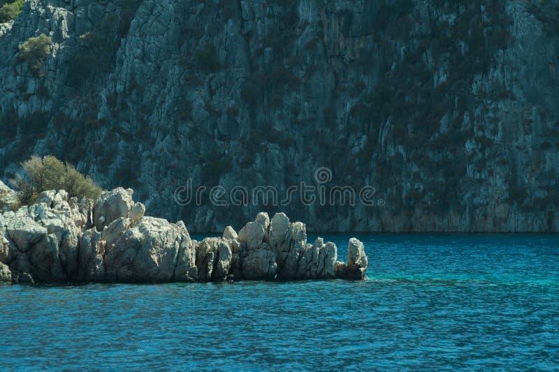 Berg en Overzees kustlijn met een rotsachtergrond royalty-vrije stock afbeelding