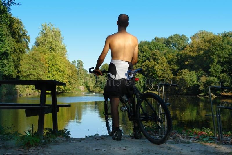 Berg-fietser die vijver overziet. stock afbeeldingen