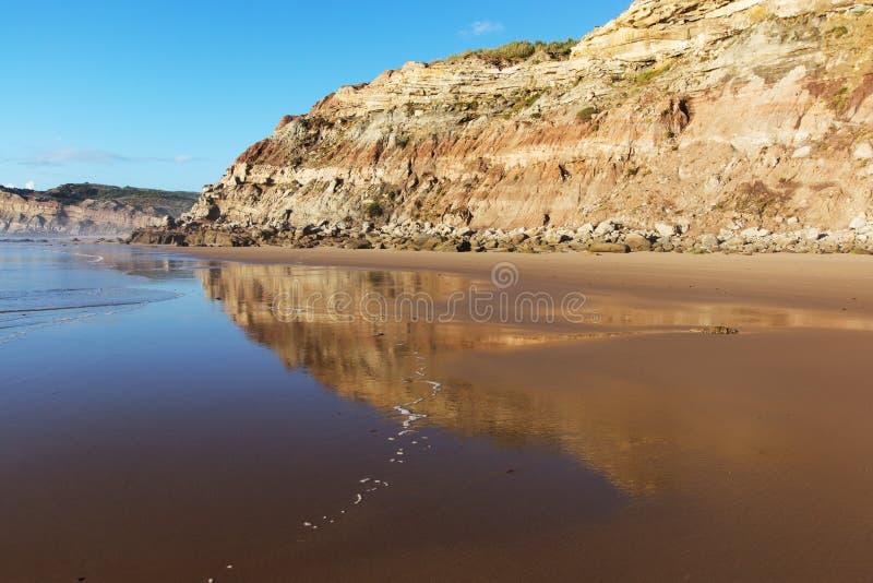 Berg in het vlotte water van het strand Areia Branca wordt weerspiegeld die Lourinha, Portugal, stock foto